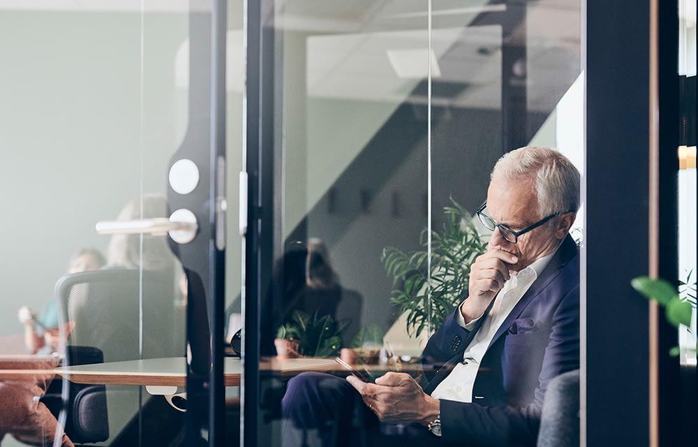 Swing House, työntekijä lukee sähköpostin kännykästä neuvotteluhuoneessa